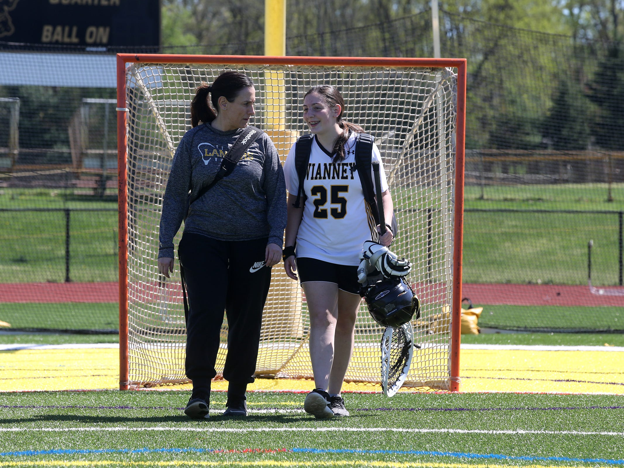 Teresa DiMezza, who is on a leave of absence from coaching the St. John Vianney girls lacrosse team, due to having a stroke late last year, walks with her daughter, Maddie, who is the goalie for the team, before a game against Neptune at St. John Vianney High School in Holmdel, NJ Wednesday, April 24, 2019.