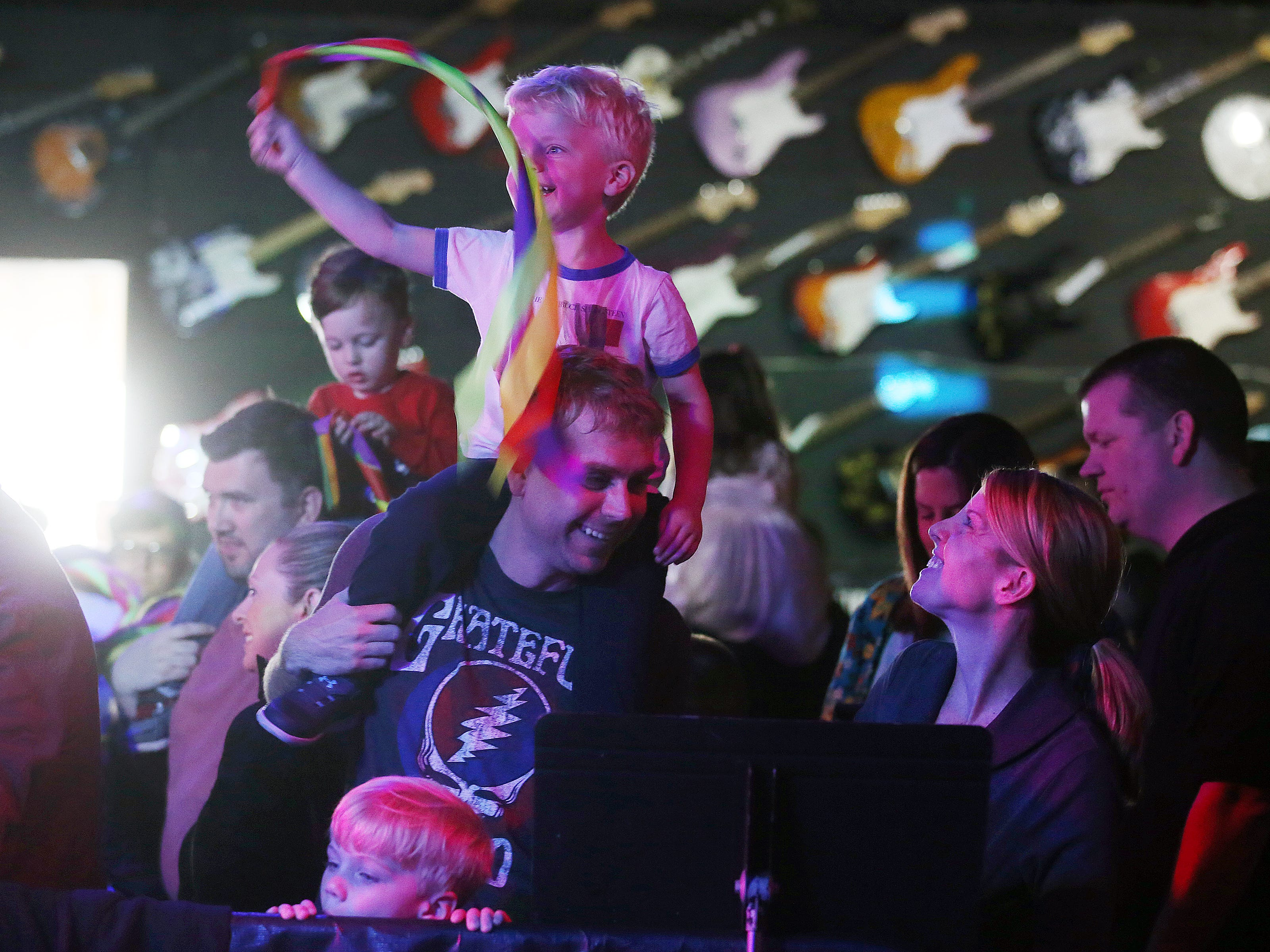 Danielle and Brandon Crosby of Ocean Twp. dance with their sons, (on shoulders) Ryan, 3, and (standing in front) Dylan, 5, as the Rock and Roll Playhouse presents the Music of Bruce Springsteen for Kids at the Stone Pony during the Asbury Park Music and Film Festival in Asbury Park, NJ Sunday, April 28, 2019.  #APMFF