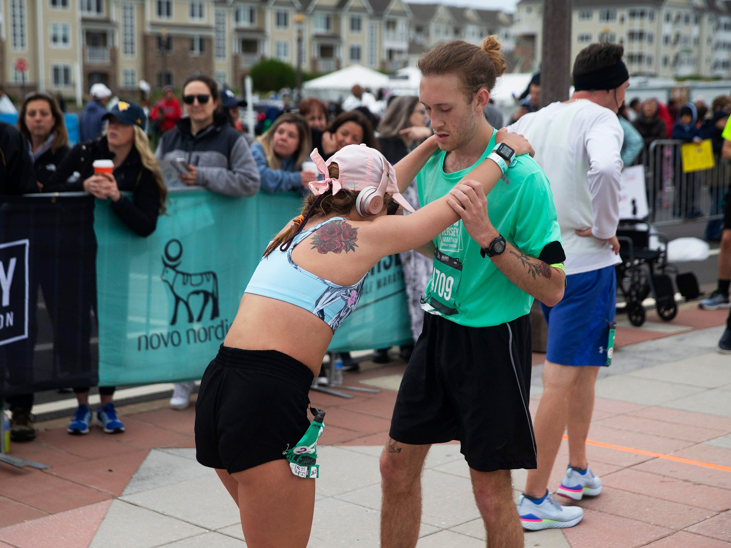 A tired runner is helped down the chute after crossing finish line in the half marathon. 2019 Novo Nordisk New Jersey Marathon and Half Marathon which started at Monmouth Park in Oceanport and ended at Ocean Promenade in Long Branch.