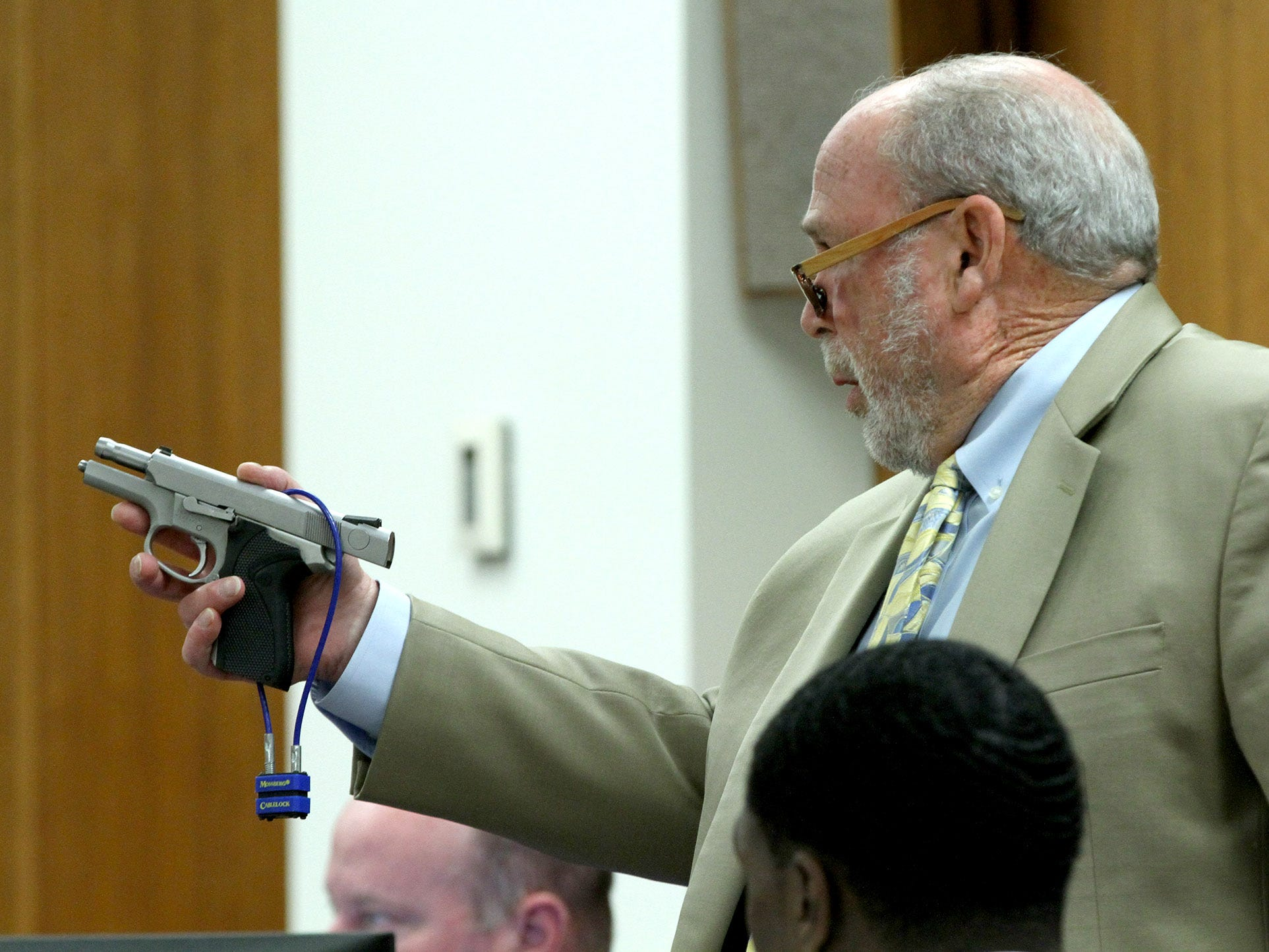 Attorney Paul Zager holds the handgun Tuesday, April 30, 2019, that his client Dante Allen is charged with using to shoot Asbury Park police Officer Terrance McGhee.  Allen is on trial in State Superior Court in Freehold charged with the officer's attempted murder.