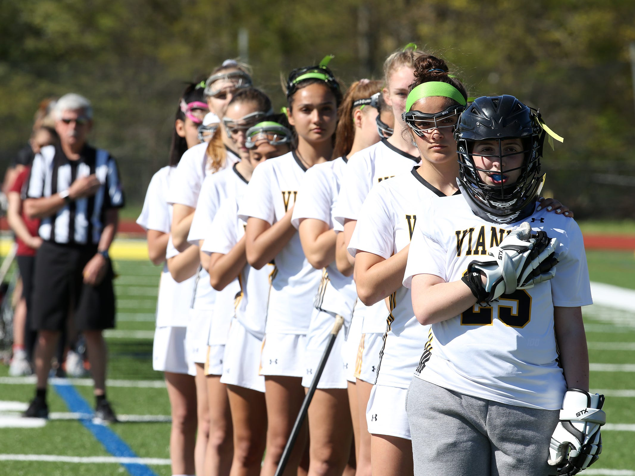 Maddie DiMezza, daughter of Teresa DiMezza, who is on a leave of absence from coaching the St. John Vianney girls lacrosse team, due to having a stroke late last year, salutes the American flag with her team before playing goalie during a game against Neptune at St. John Vianney High School in Holmdel, NJ Wednesday, April 24, 2019.