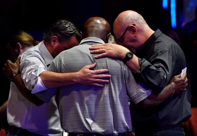 Men embrace and bow their heads during an early National Day of Prayer observance in 2019. Social distancing will be practiced this year, with a parking lot worship event planned.