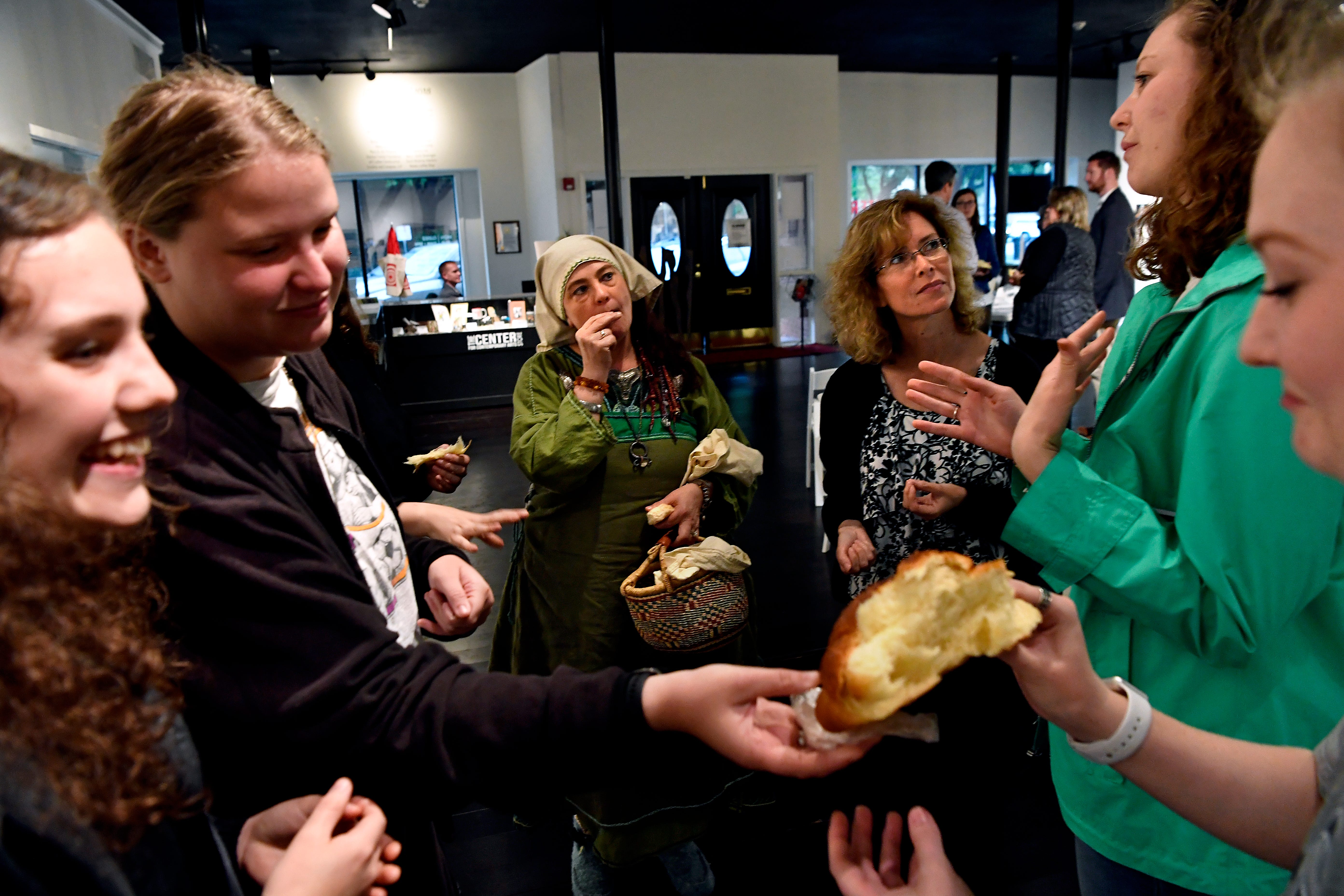 Avalon Olson Zakazakina (center) a norse pagan, and Angela Nicolini listen to Madison Boboltz as Caitlin Dunnells passes bread to Elizabeth Pullman on Thursday at the Center for Contemporary Arts. Brookley Baker watches. The gallery was the site for the Abilene Interfaith Council's observance of the National Day of Prayer, which concluded with differing believers sharing bread.