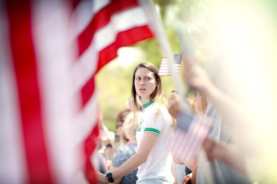 Shelby Tomassi, a senior at UNCC, holds an American flag as she watches the police escort of the body of Riley Howell, UNC Charlotte shooting victim, arrive at Wells Funeral Home in Waynesville to a hero's welcome on May 2, 2019. Police say that Howell's actions during the shooting cost him his life and saved the lives of others.