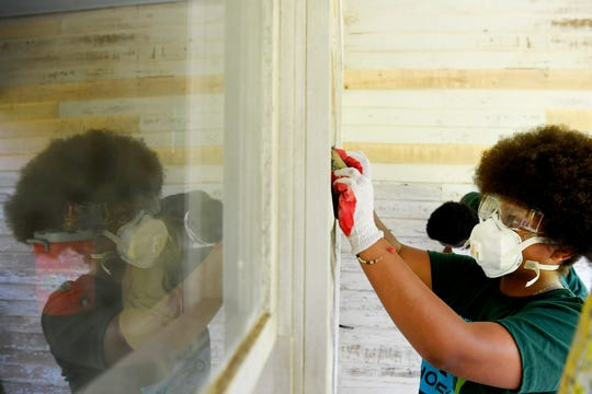 Jacenia Hawkins prepares the porch of Nina Simone's birthplace for a fresh coat of paint in Tryon May 2, 2019.