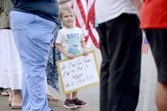 Maddox Hunter, 4, watches news helicopters as the police escort of the body of Riley Howell, UNC Charlotte shooting victim, approaches Wells Funeral Home in Waynesville on May 2, 2019. Police say that Howell's actions during the shooting cost him his life and saved the lives of others.