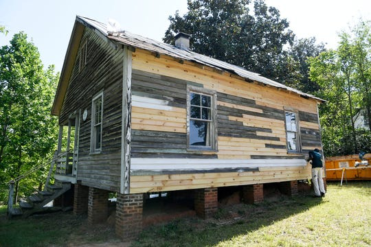 Tyle Woodard, 17, paints the birthplace of Nina Simone in Tryon, N.C., on May 2.