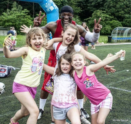 """James """"Quice"""" Williams (back), a former professional football player from Battle Creek, has organized the inaugural City Kids Day on Saturday, May 4 at the Battle Creek Central Fieldhouse."""