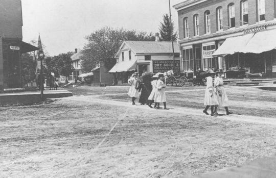 Girls crossing the street in the Village of Whitney Point near the site of John Paterson's house, about 1900.
