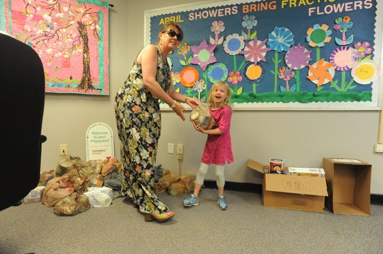 Black Mountain Primary kindergarten teacher Noelle Harralson hands a student a bag of food on May 2, when her class delivered items raised in the school's annual food drive to Swannanoa Valley Christian Ministry.