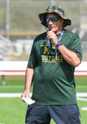 Melbourne Central Catholic head football coach Walt Ramsay talks with his players during spring football practice at the school.