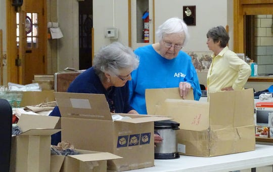Jan Baldwin, Donna Smith and Sandra Neumann prepare items for the rummage sale on Wednesday at St. Paul's Lutheran Church. The sale continues through Saturday.