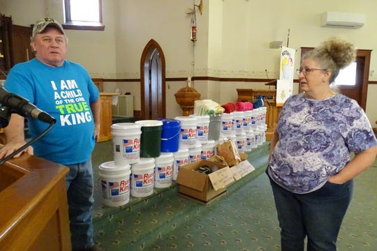 The Rev. Mike Greenler of St. Paul's Lutheran Church and his wife, Jane, display the five-gallon buckets the congregation is sending to help flooding victims in Nebraska.