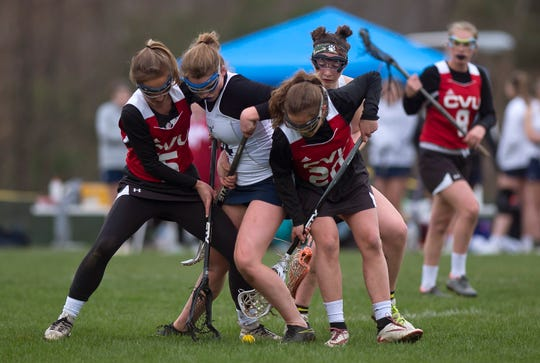 Mount Mansfield's Caitlin Boyarsky, center, fights for a ground ball between Champlain Valley's Petra Kapsalis, left, and Ava Bartlett during Wednesday's girls lacrosse game in Jericho on May 1, 2019.