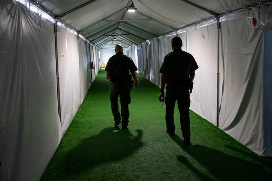 Customs and Border Protection agents walk down the hallway in U.S Customs and Border Protection's new temporary detention facility for migrants near the Donna-Rio International Bridge in Donna, Texas, on Thursday, May 2, 2019.