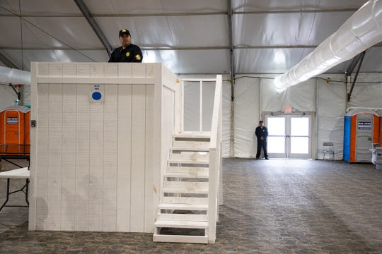Guards watch during a media tour in a dormitory that will house as many as 125 migrants in U.S Customs and Border Protection's temporary detention facility near the Donna-Rio International Bridge in Donna, Texas, on Thursday, May 2, 2019.