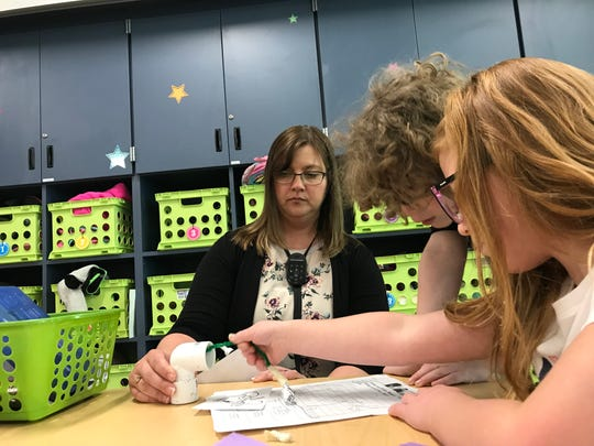 """Jennifer Huff holds a model """"flower"""" as first grade students test their pollinator. Their challenge was to pick up glitter and distribute it onto a sheet to represent pollination."""