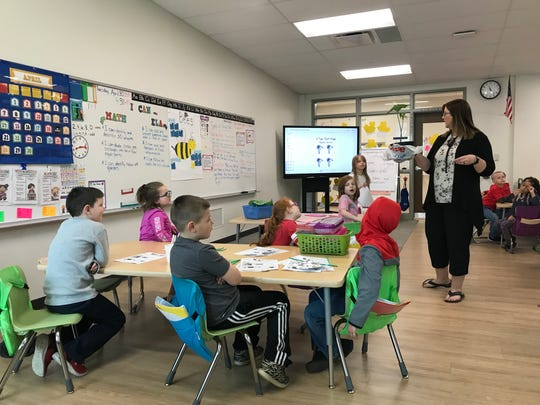 First-grade teacher Jennifer Huff shows students a real example of a flower they will be testing. The Chillicothe Primary STEM program aims at bringing students and the real world together.