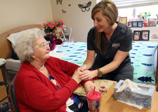 Toni Powell, right, checks in with Tootsie Davidson at the Forest Hills Care Center in Newtown.
