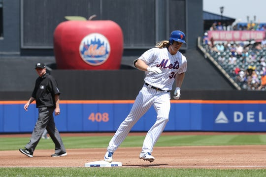 New York Mets starting pitcher Noah Syndergaard (34) rounds the bases after hitting a solo home run against the Cincinnati Reds during the third inning at Citi Field.
