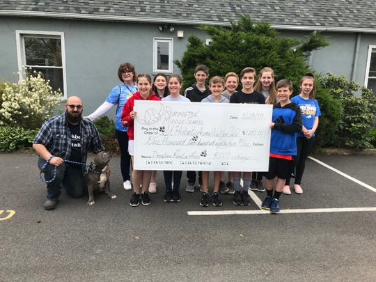 Many 6th graders participated in the Read-a-Thon, the picture is of a handful of students who went to deliver the check. First row left to right: Alex Falcone (St. Hubert's Asst. Manager), Mr. Bubbles (dog available for adoption), Emily Steinberg, Brooke Stange, Cameron Hess, Dylan Reynolds, Jack Heppner Back Row from left to right: Beth McGivney, Samantha Sova, Nicolas Borella, Mason Quintard, Mary Mele, Anna Bennington