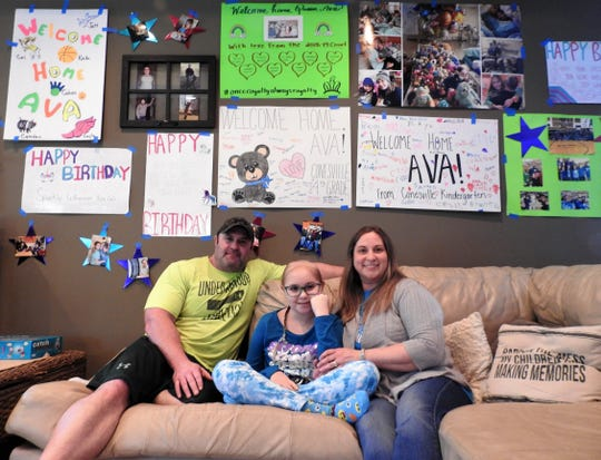 Dan, Ava and Melissa Winner at their home with several welcome home signs on the wall. Ava recently returned home and is undergoing chemotherapy treatments for a brain tumor detected in January. After three surgeries in Akron, Ava went to Cincinnati for proton radiation.