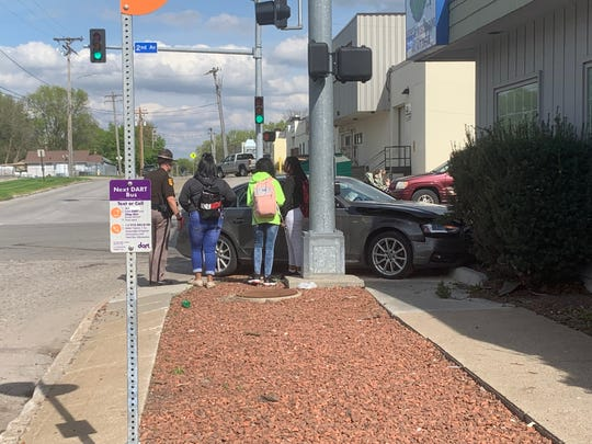 An Iowa State Patrol trooper speaks with witnesses of crash Thursday, May, 2, 2019 at the intersection of Second and Douglas avenues on Des Moines' north side. A gray-colored Audi A4, right, crashed into students getting off a DART bus after the Audi was struck by a Hyundai Sonata. Trooper say the driver of the Sonata has been cited and the victims are expected to survive.