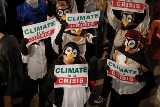 A group of Biden supporters dressed up as penguins and held up Climate is a Crisis signs during democratic presidential candidate hopeful Joe Biden's campaign stop in Des Moines on Wednesday, April 30, 2019.