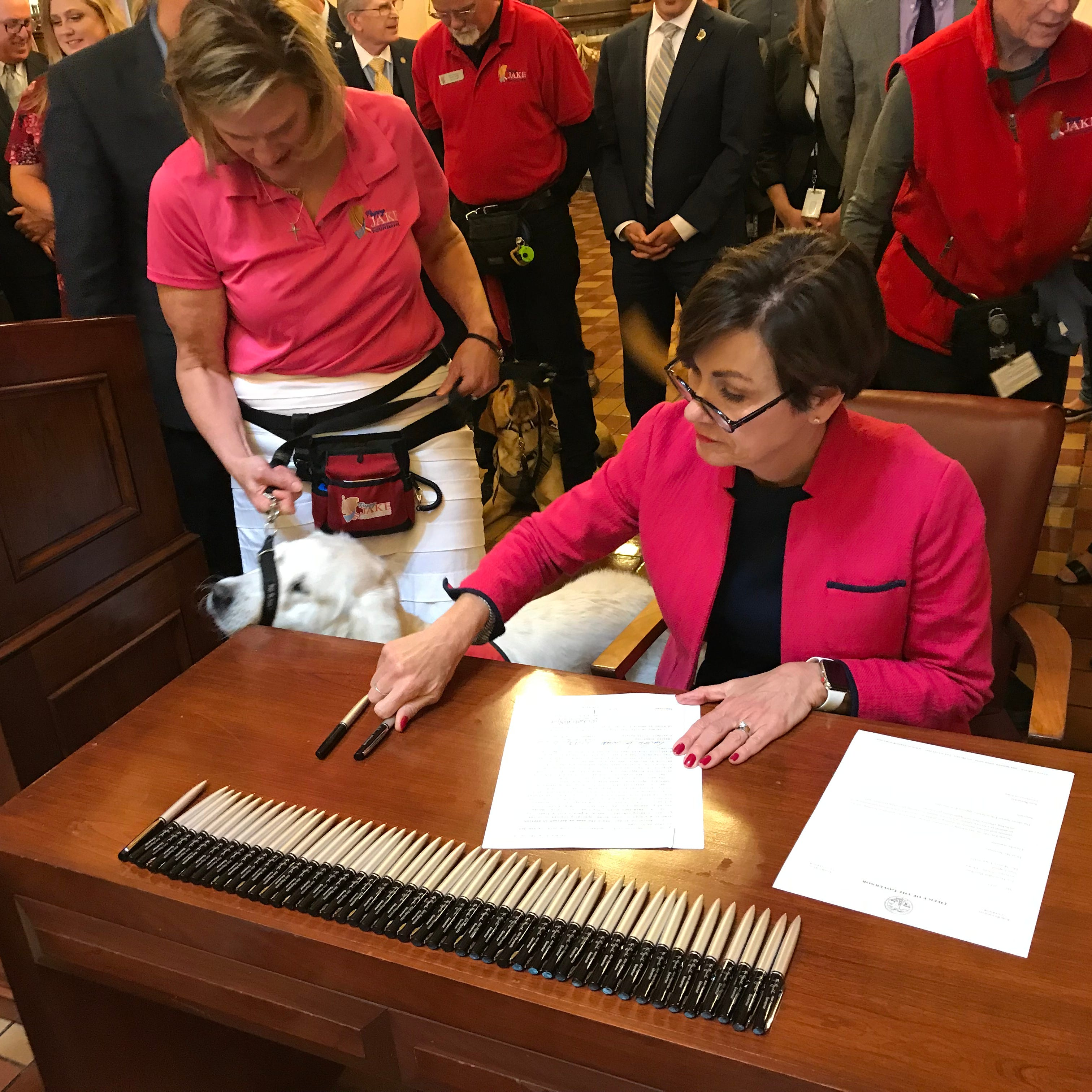 With service dogs watching, Kim Reynolds signs bill on service animals