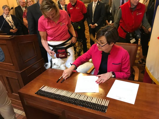 Gov. Kim Reynolds signs a bill creating penalties for lying about a service animal on Thursday, May 2, 2019. Kris Fish Kuhlmann stands nearby with service dog Captain Bill, named for a World War II army medic named Capt. William Hodges.