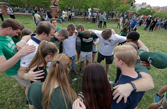 Students pray together during a vigil at the University of North Carolina-Charlotte in Charlotte, N.C., Wednesday.