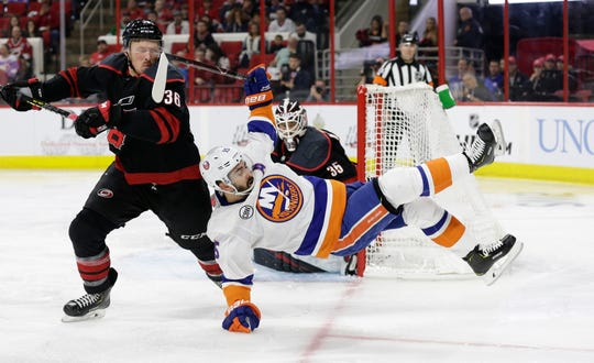 Carolina Hurricanes' Patrick Brown (36) takes a stick to the face while chasing the puck with New York Islanders' Cal Clutterbuck (15) during the second period of Game 3.