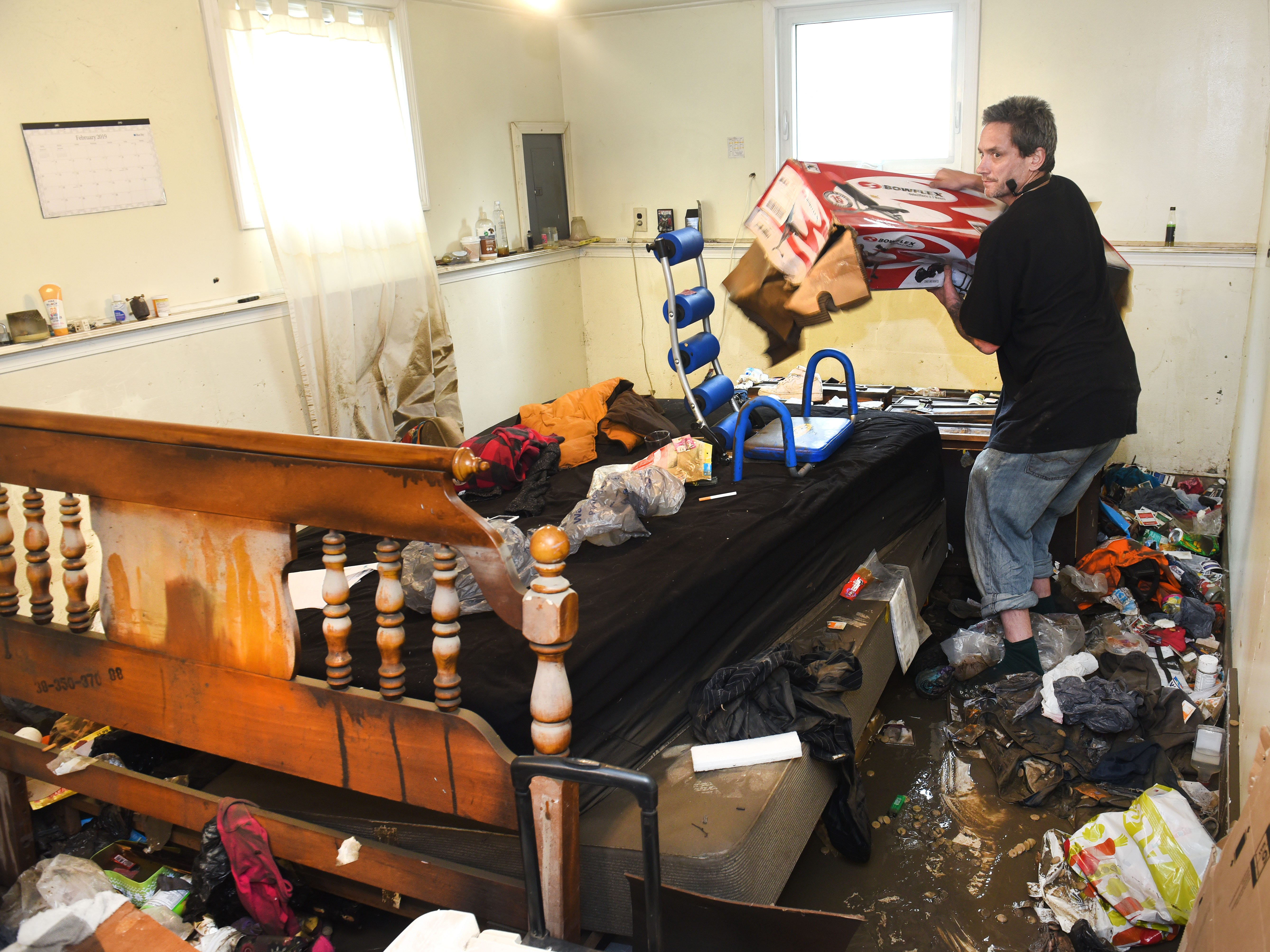 Jesse Sorrell of Dearborn Heights tosses items while cleaning out a bedroom in his flood-damaged basement.