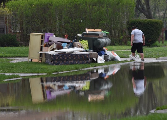 A boy splashes through flood waters at his home along Eaton Avenue in Dearborn Heights as ruined family belongings damaged by flood water are piled at the curb on May 2, 2019. M