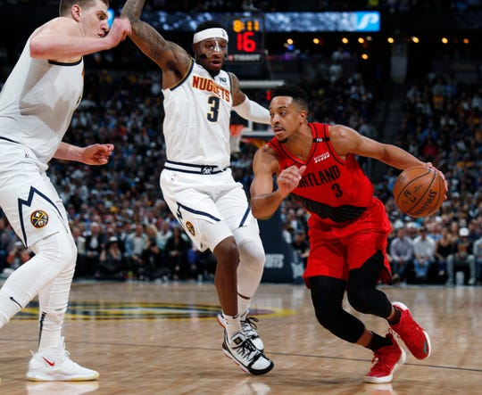 Portland Trail Blazers guard CJ McCollum, right, drives past Denver Nuggets forward Torrey Craig and center Nikola Jokic, left, during the second half of Game 2 Wednesday. Portland won 97-90.