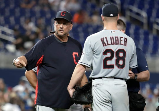 Cleveland Indians manager Terry Francona, left, stands on the mound with starting pitcher Corey Kluber (28) during the fifth inning Wednesday. Kluber was hit by a single hit by Marlins' Brian Anderson.