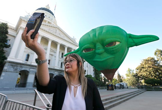 State Sen. Ling Ling Chang poses for a selfie with a hot air balloon shaped like Yoda of Star Wars, outside the Capitol Thursday, May 2, 2019, in Sacramento, Calif.
