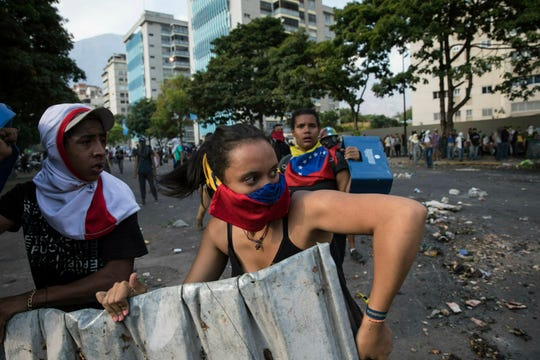 Anti-government protesters clash with the National Guard near the La Carlota airbase in Caracas, Venezuela, Wednesday, May 1, 2019.