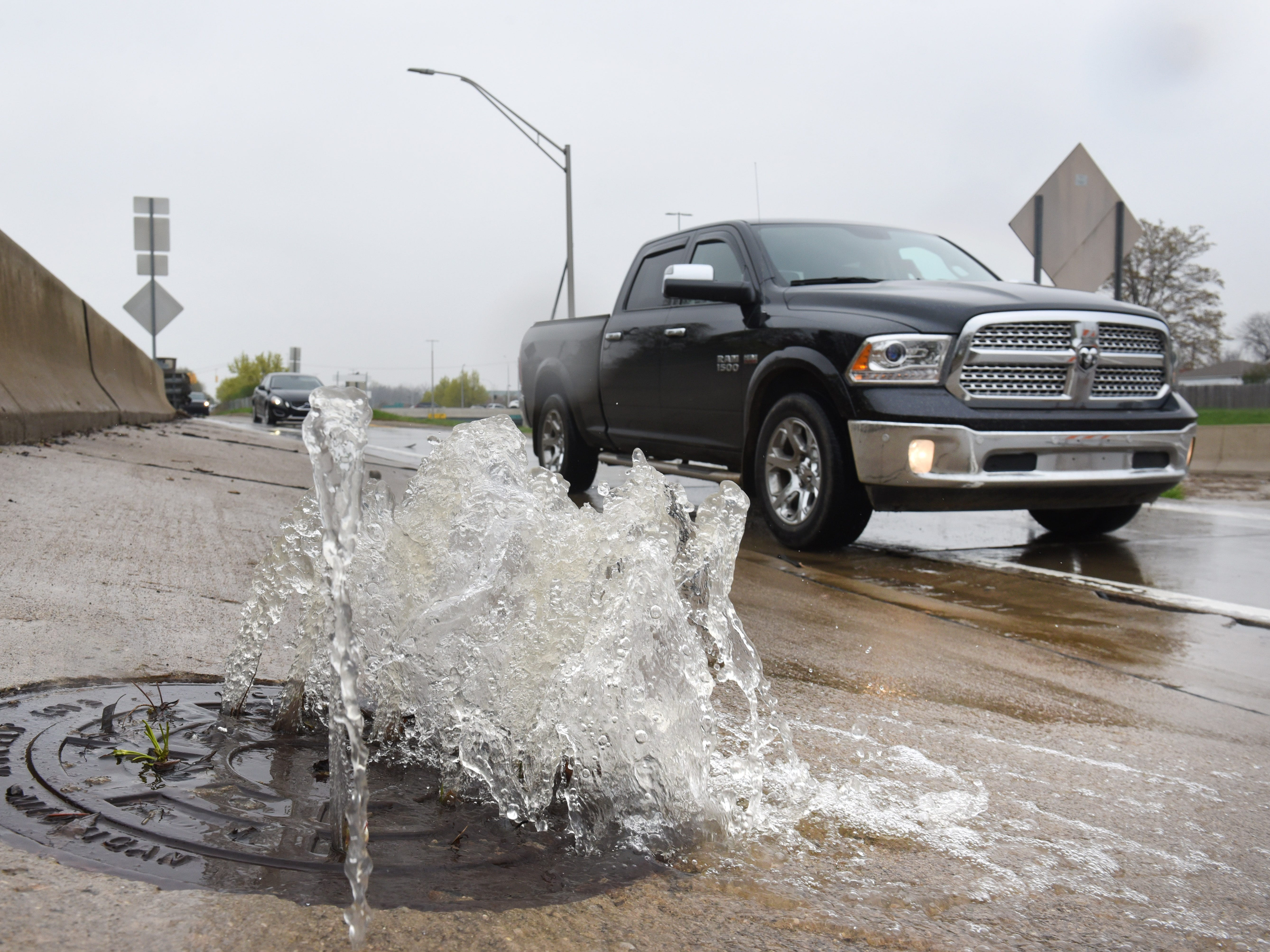 Water shoots out of a manhole cover along the Southfield Road service drive as motorists are detoured off Southfield Road at Outer Drive to avoid floodwaters.