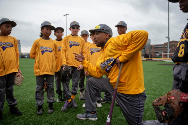 Dytarious Edwards, coach of the 11U Detroit Rangers, talks with his team before a Police Athletic League scrimmage against the YMCA Tigers at The Corner Ballpark.