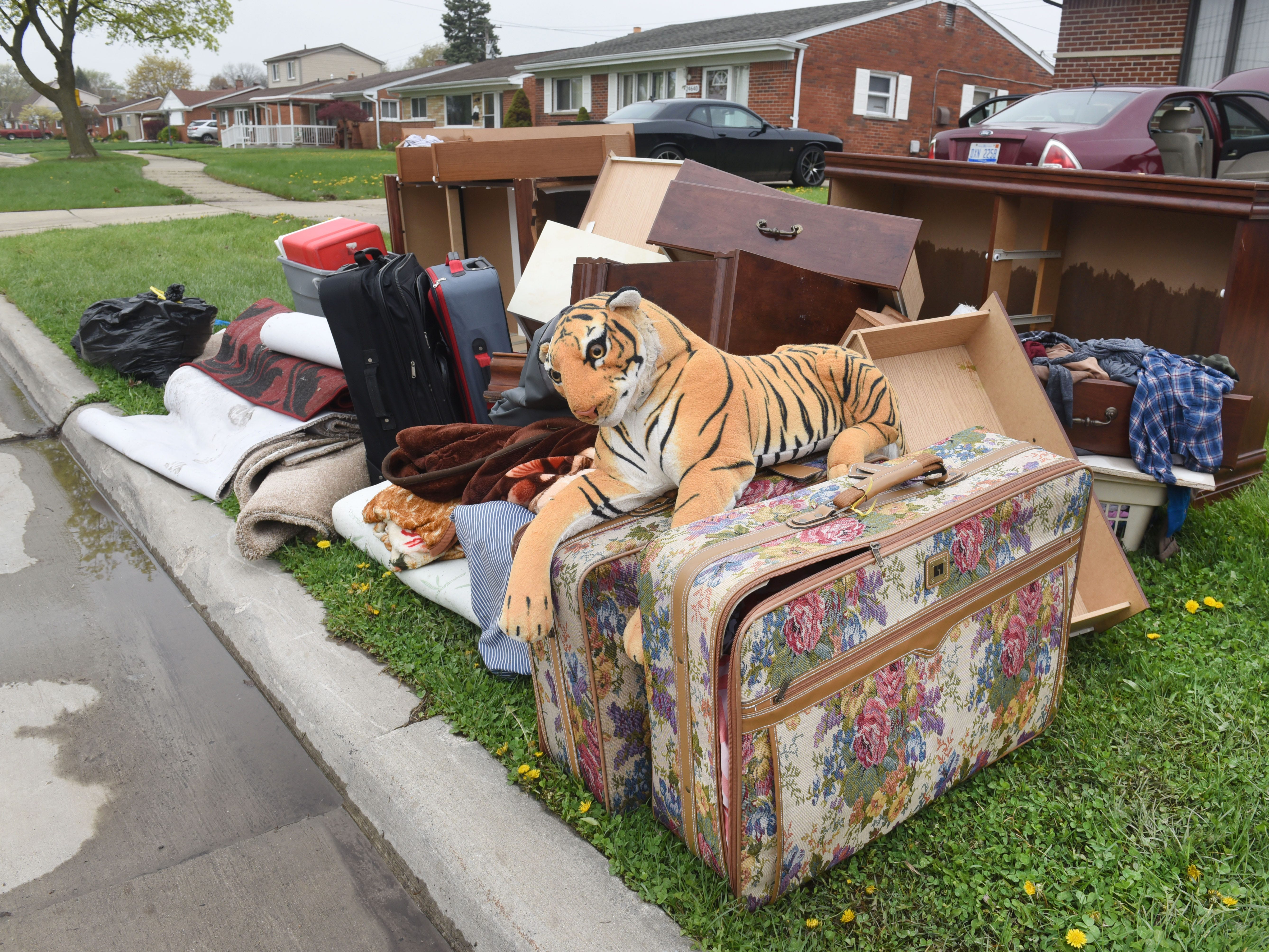A stuffed animal, rugs and furniture sit curbside after being dragged out of a flood-damaged home on Currier Street in Dearborn Heights Thursday.