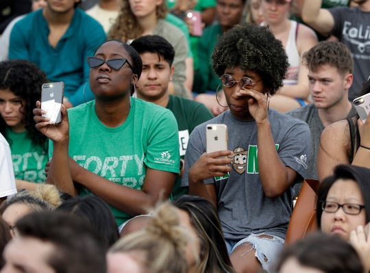Students flash phone flashlights during a vigil at the University of North Carolina-Charlotte in Charlotte, N.C., Wednesday, May 1, 2019 after a student with a pistol killed two people and wounded four others on Tuesday.