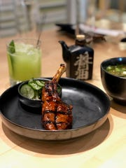 The gochujang-marinated lamb chop is served with three chops, plus hijiki (sea vegetable) and thinly-sliced cucumber.