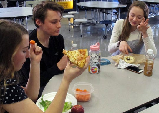 Burlington High School student Emma McCobb, left, holds a piece of pizza while eating with classmates in the school cafeteria in Burlington, Vt.