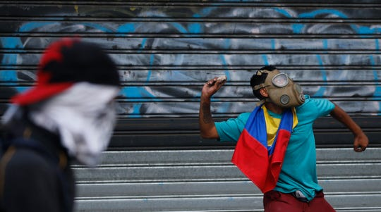 An anti-government protester winds up to throw a rock at security forces during clashes between the two, in Caracas, Venezuela, Wednesday, May 1, 2019.