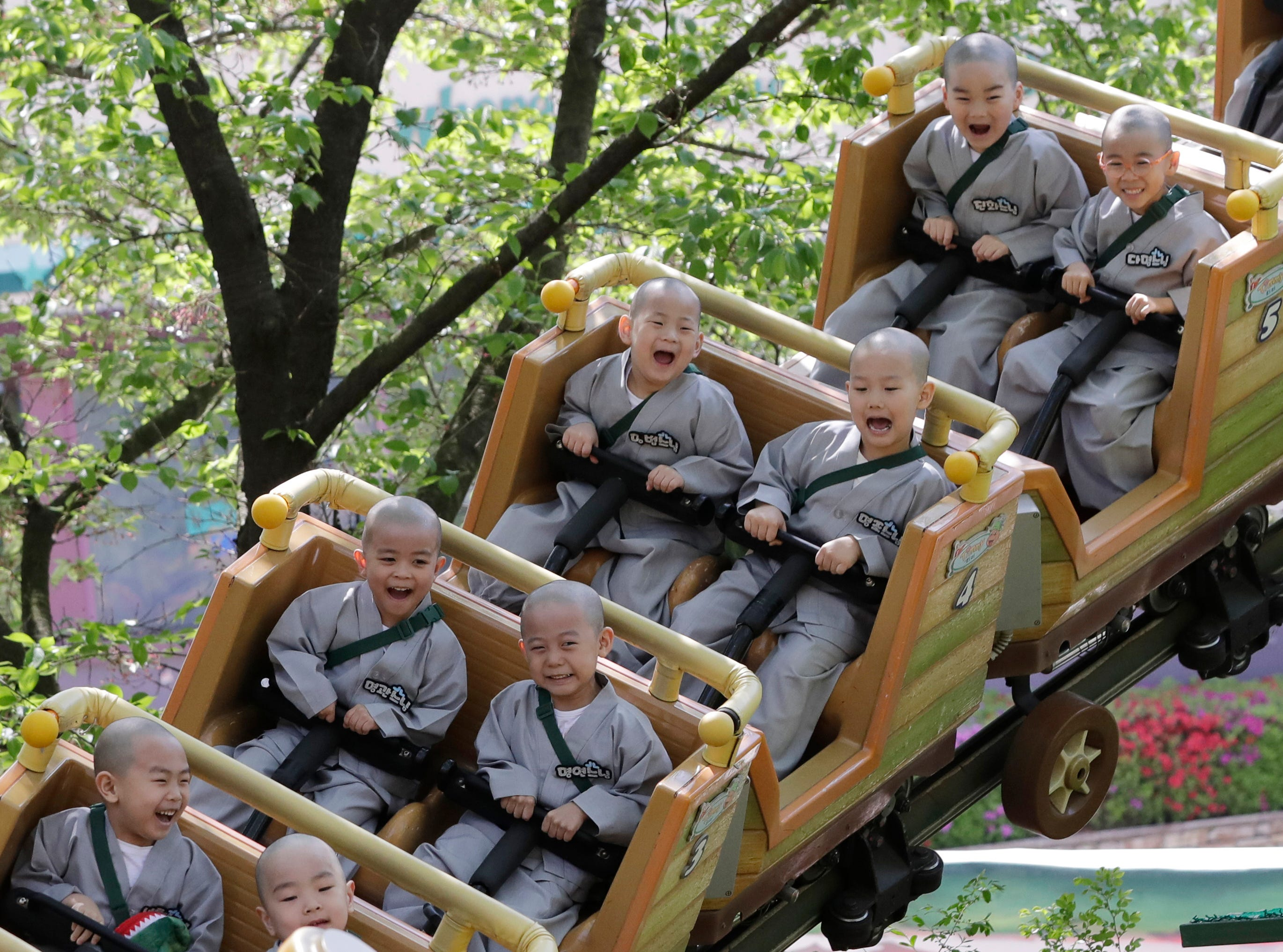 Shaven-headed children ride a roller coaster at the Everland amusement park in Yongin, South Korea, Thursday, May 2, 2019. Ten children entered a temple to have an experience of monks' life for three weeks. Buddhists visit a temple across the country to celebrate the Buddha's upcoming birthday on May 12.