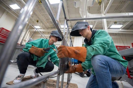 Students Justin Ngo, left, and Alex Seba, assemble a go-kart at Novi High's power technology lab.