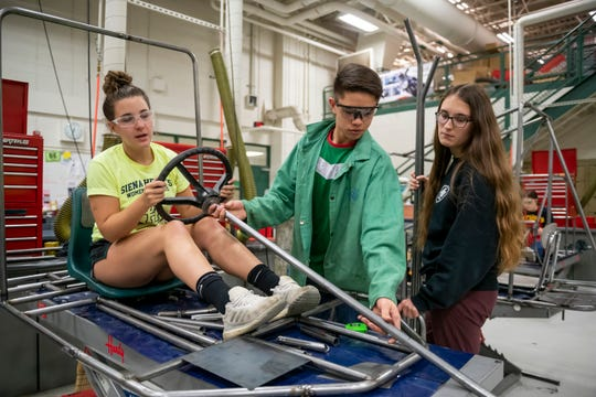 Emily Pringle, left, Luis Acosta, and Olivia Hudson build a go-kart in the power technology lab at Novi High. The career technical education program uses expensive machines and equipment prepare students for jobs.