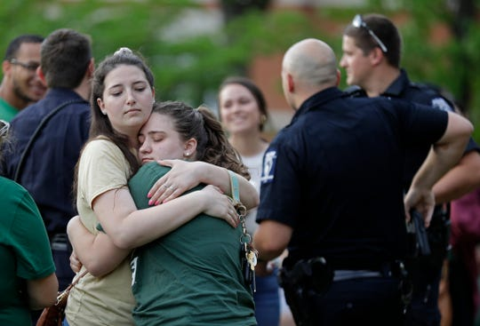 Two students hug during a vigil at the University of North Carolina-Charlotte in Charlotte, N.C., Wednesday, May 1, 2019.