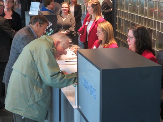 Shareholders sign into the Corning Inc. annual meeting at the Corning Museum of Glass on May 2, 2019.